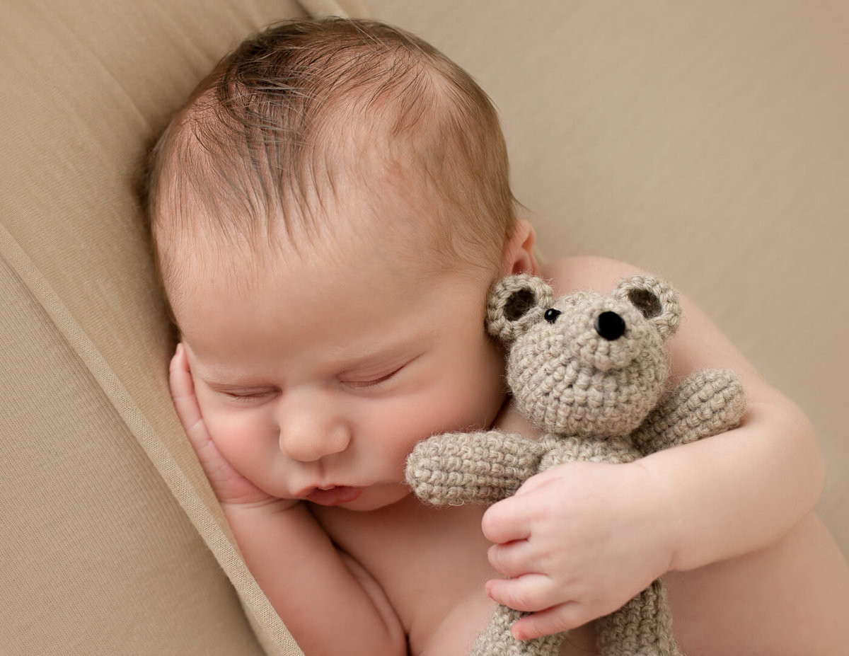 Cute newborn holding a teddy bear in our Rochester, NY studio.