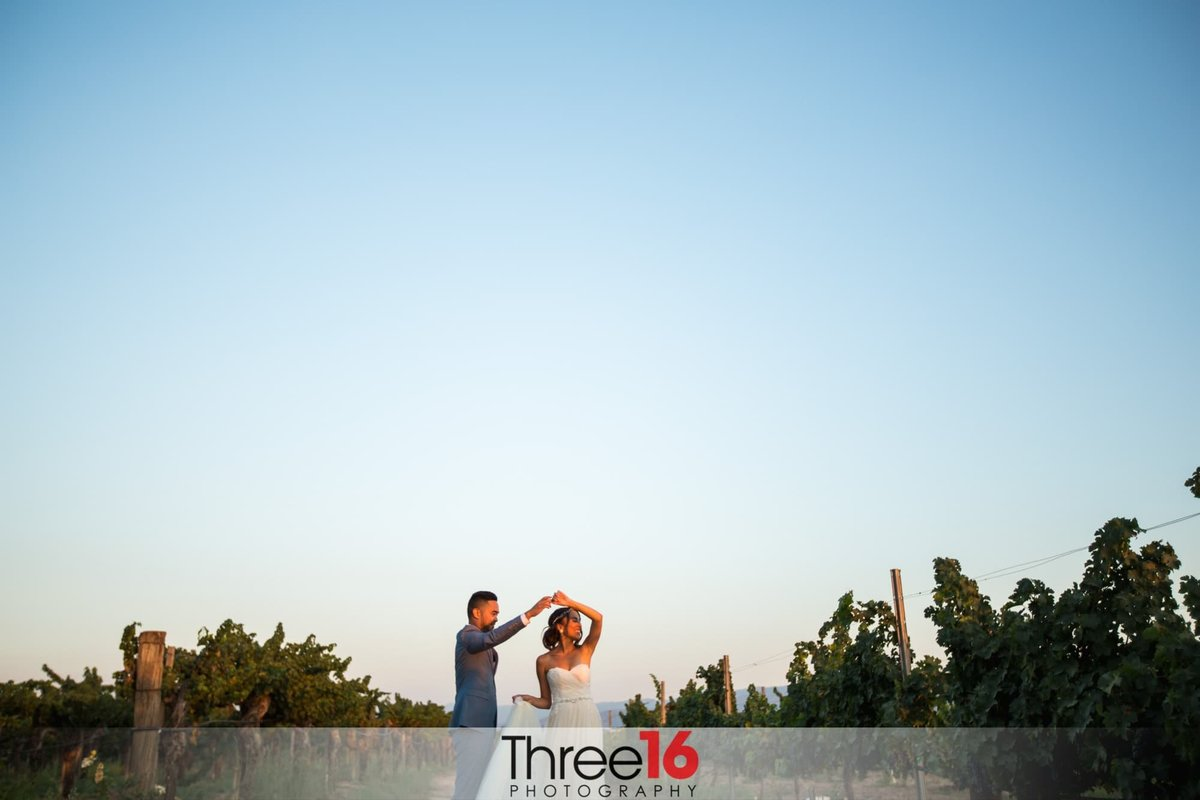 Groom twirls Bride while dancing in winery