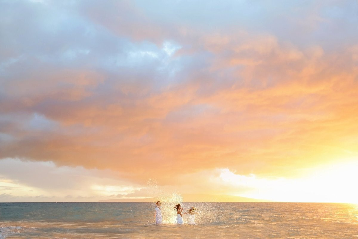 Sisters splashing eachother in the ocean during a sunset portrait shoot in Hawaii
