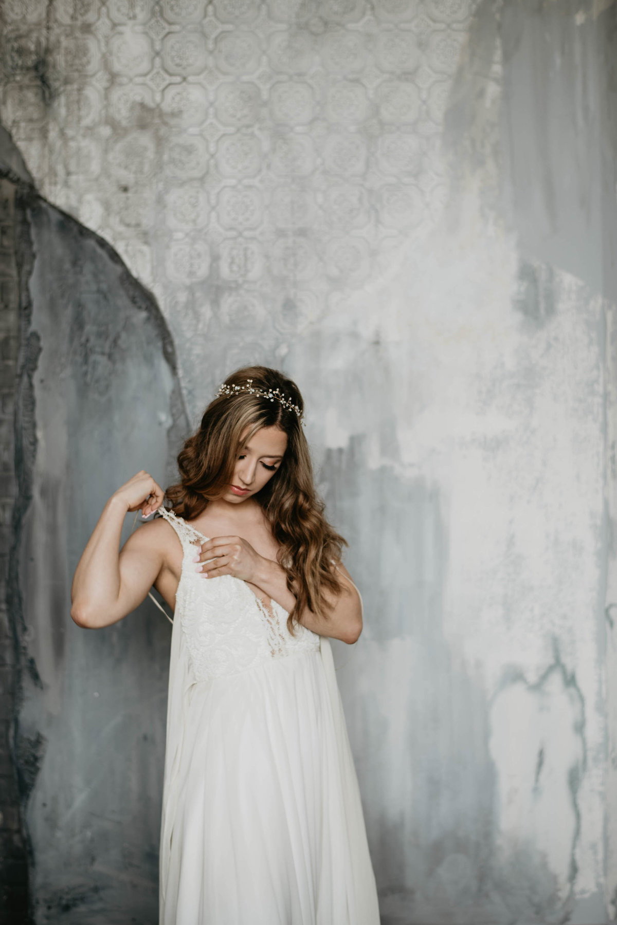 bride putting on her white wedding dress provided by Sash and Bustle