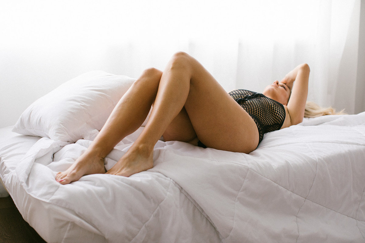 woman laying on bed during her boudoir session