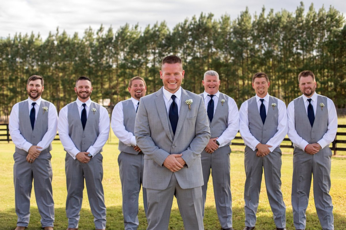 Groom standing in front of groomsmen wearing grey  suits and navy ties