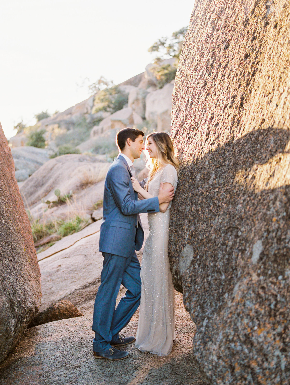 Couple embrace each other against rock - enchanted rock - engagement photos