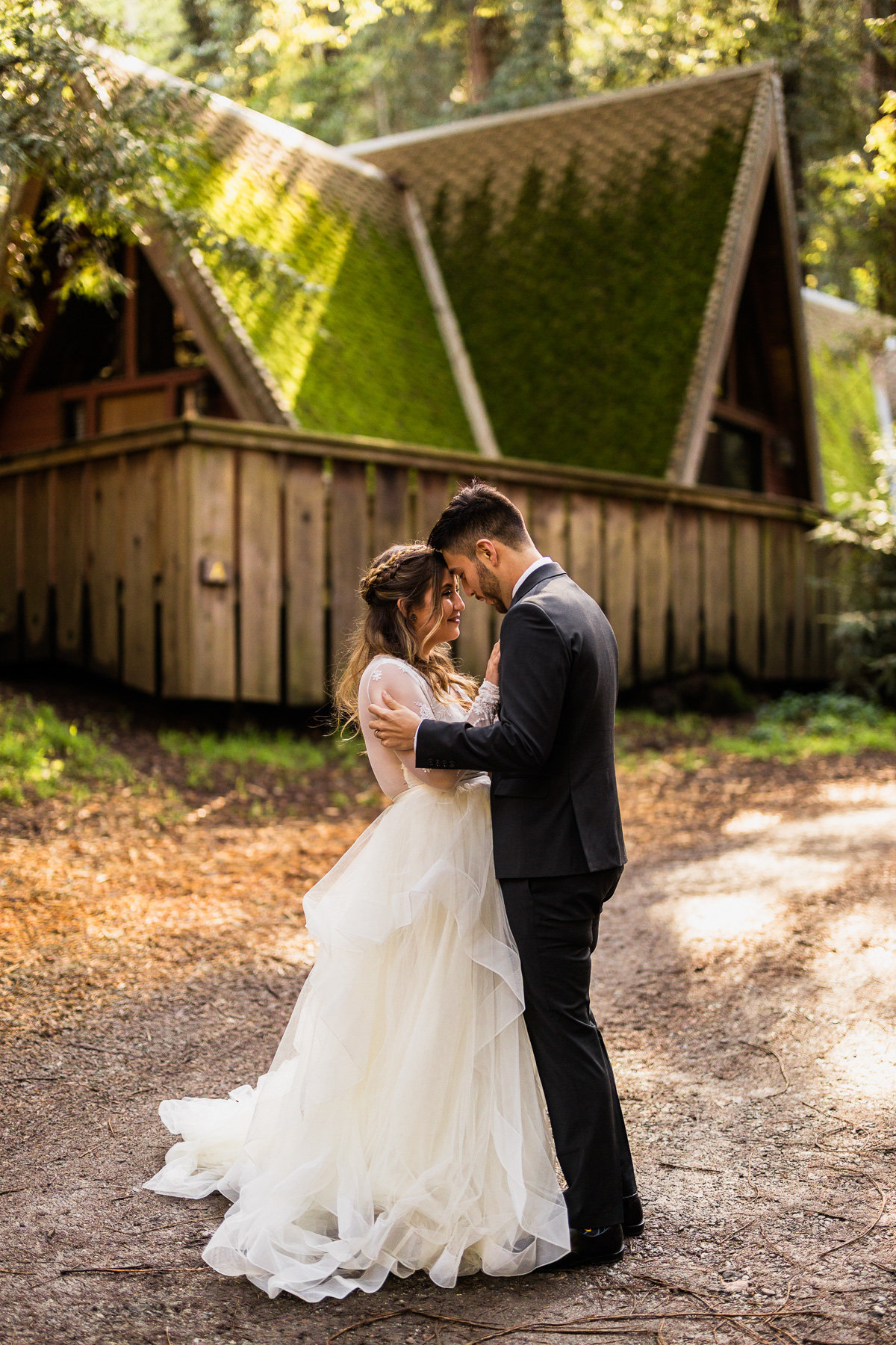Bride & groom embrace in front of a cabin the the forest before their Big Sur wedding ceremony.
