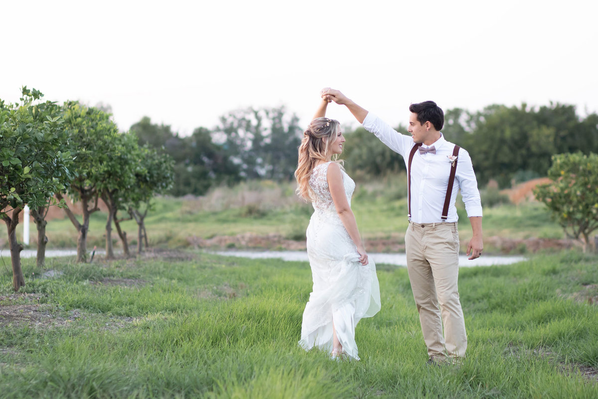 Bride and groom twirling in an orchard