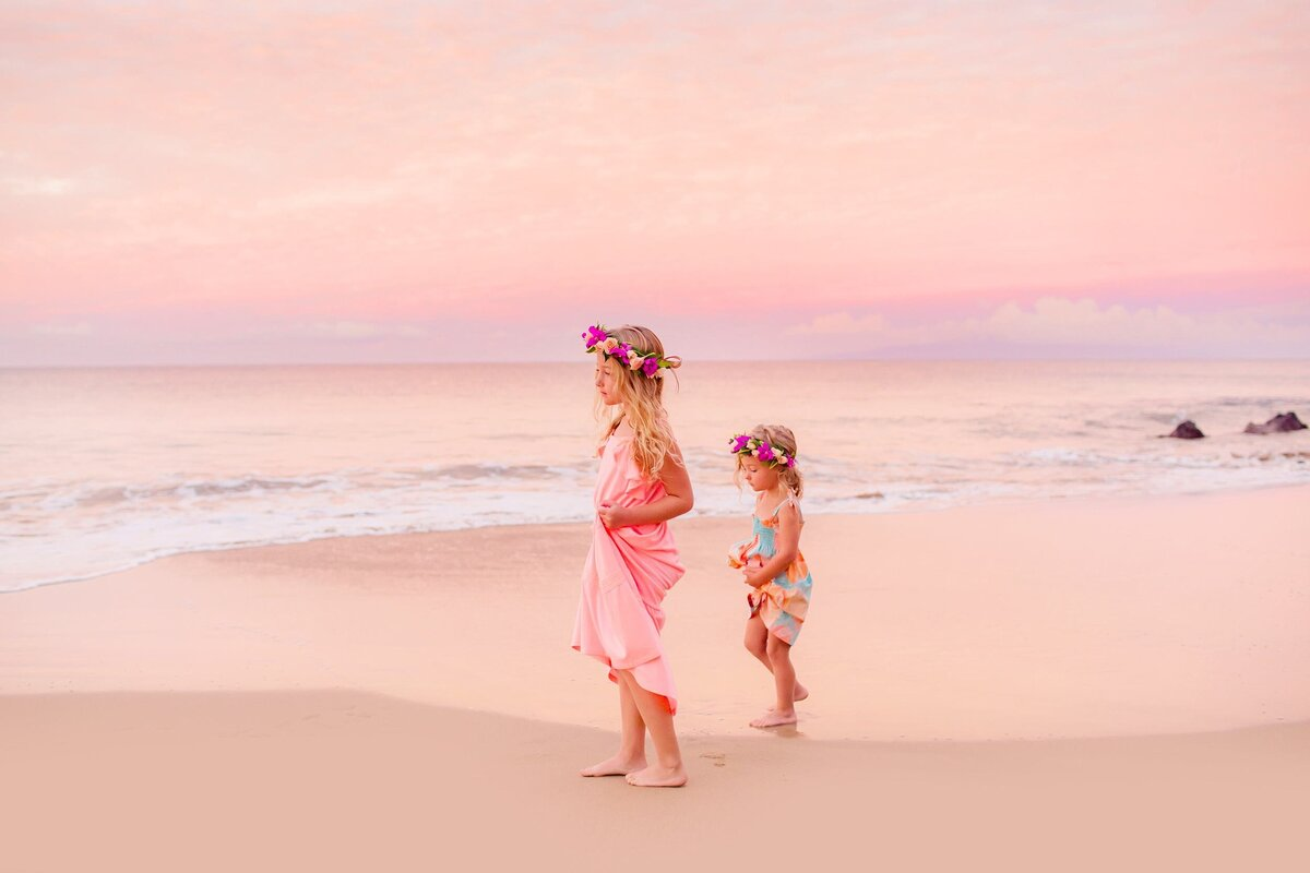 Two young girls hold their dresses and walk on the beach during a Maui sunrise session