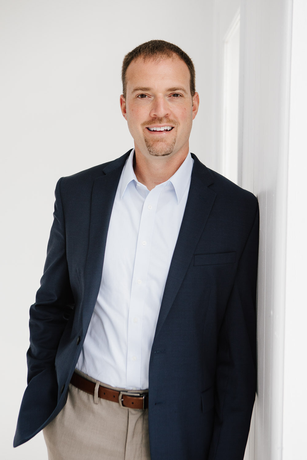Business headshot of man in suit leaning against wall