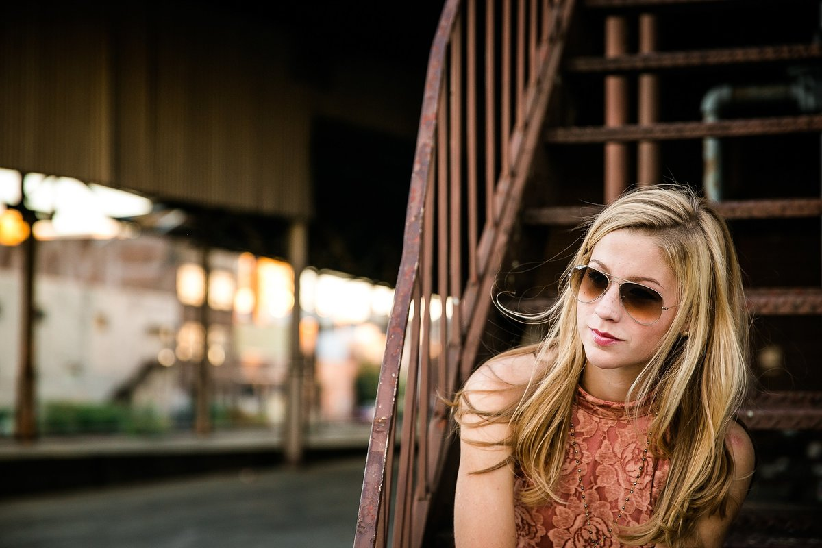 blonde-girl-sunglasses-industrial-train-station