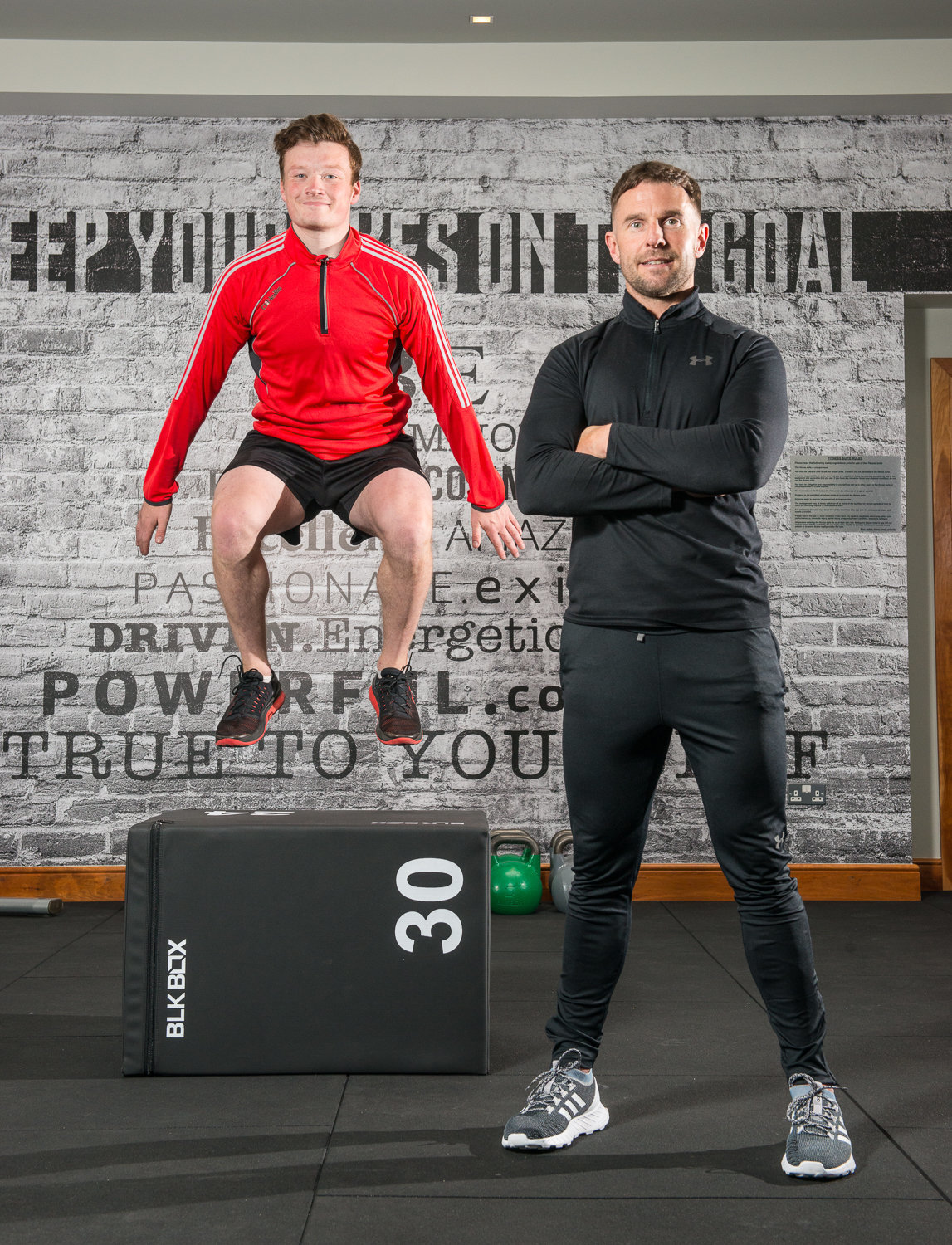 photo in gym with client jumping and fitness instructor
