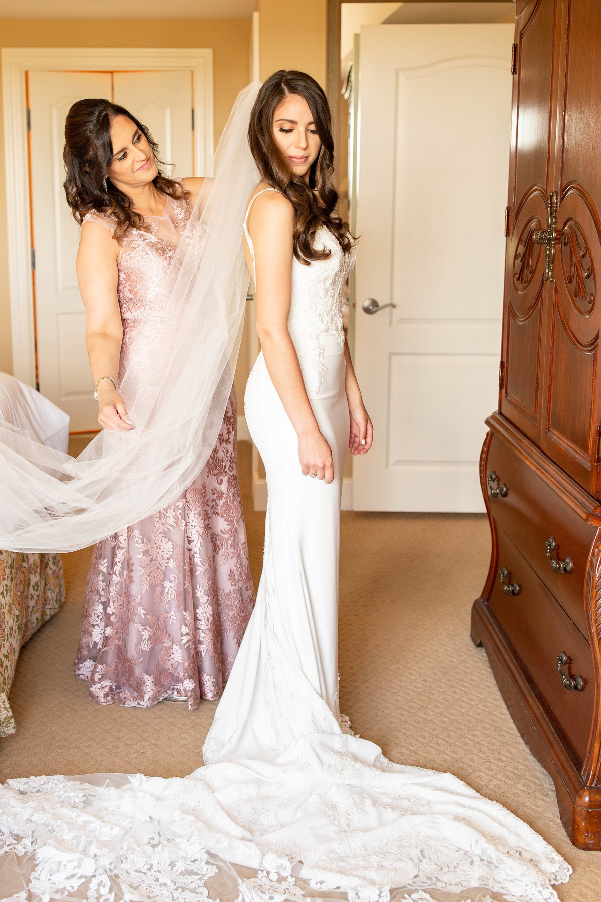 Mother of bride in blush pink dress places cathedral veil on bride's hair on her wedding day in her mermaid wedding dress