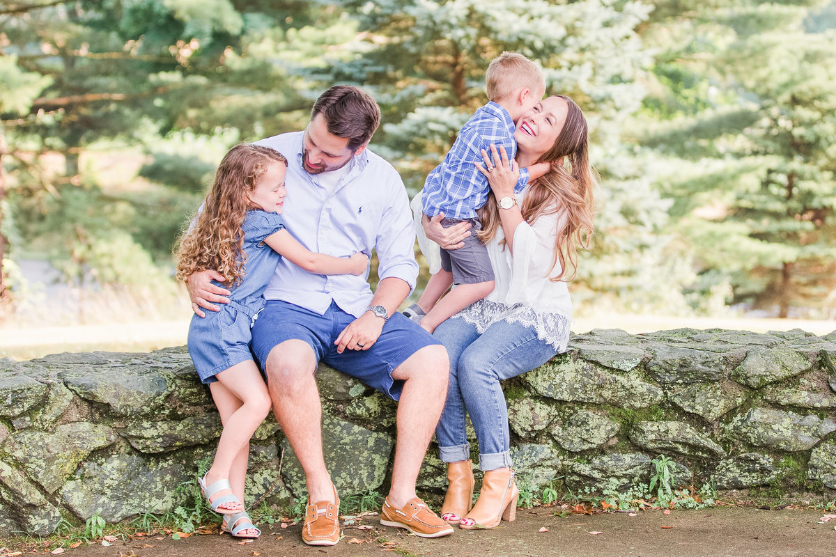 Mom and dad embrace their two young children while sitting on a stone wall outside