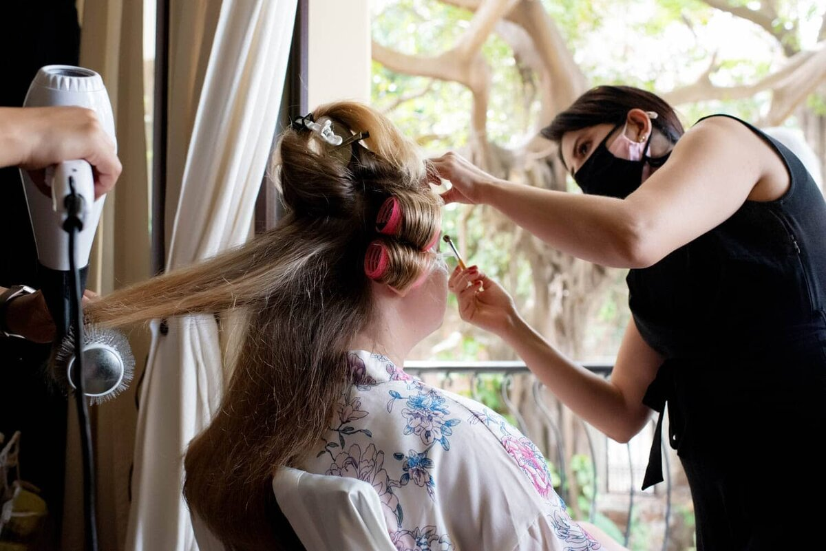 a bride with big hair curlers has two stylists working on her as she looks outside in Puerto Vallarta