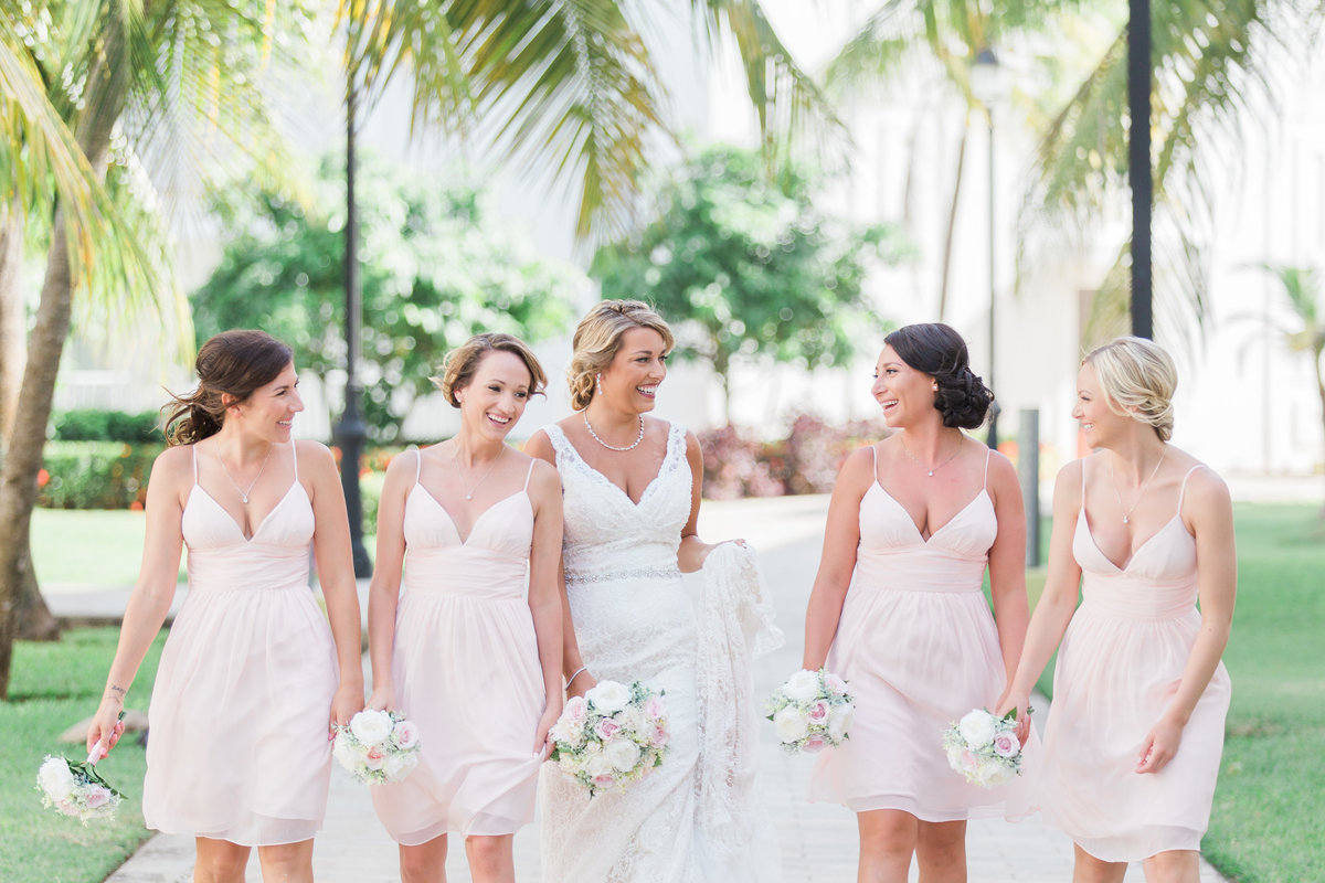 bride and bridesmaids laughing and walking outside