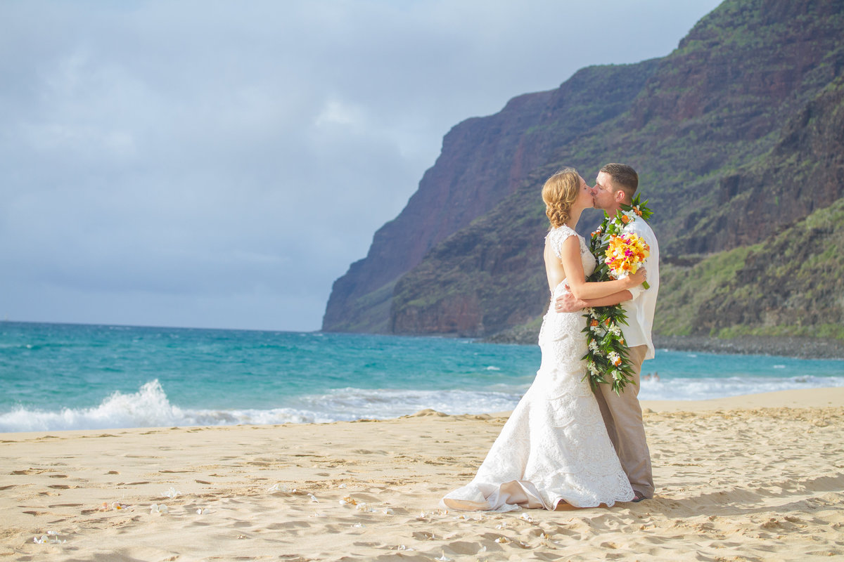 Bridal couple kissing on the beach in Hawaii.