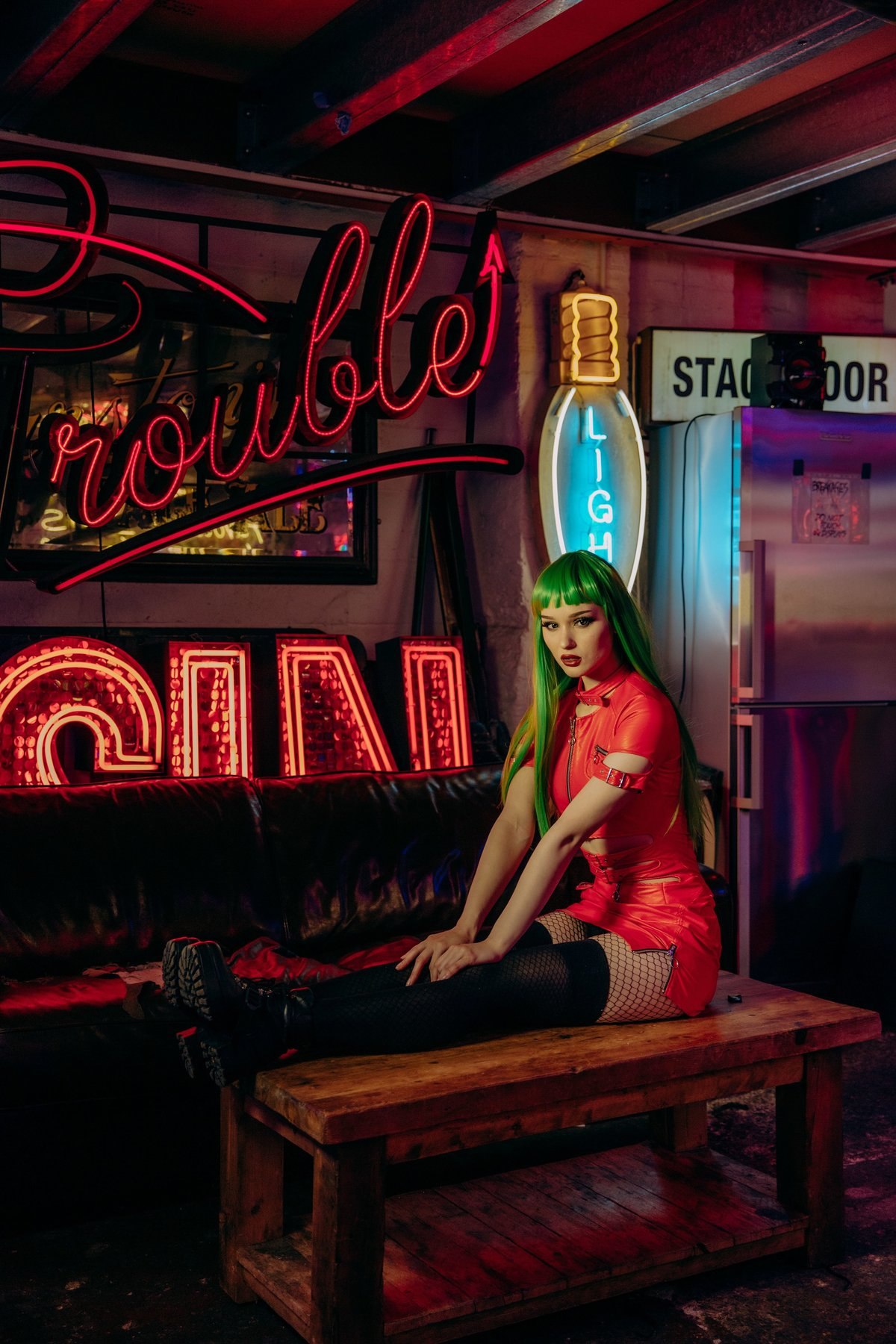 "Saida wearing a red leather dress with thigh high boots and a neon green wig, sat on a wooden table infront of a neon sign saying ""trouble"""