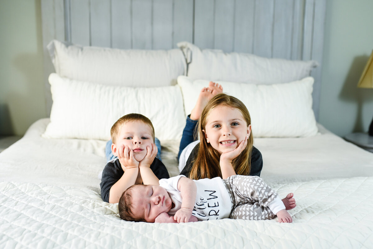 Beautiful lifestyle newborn photography: newborn boy and his siblings on their parents bed at home in Mississippi