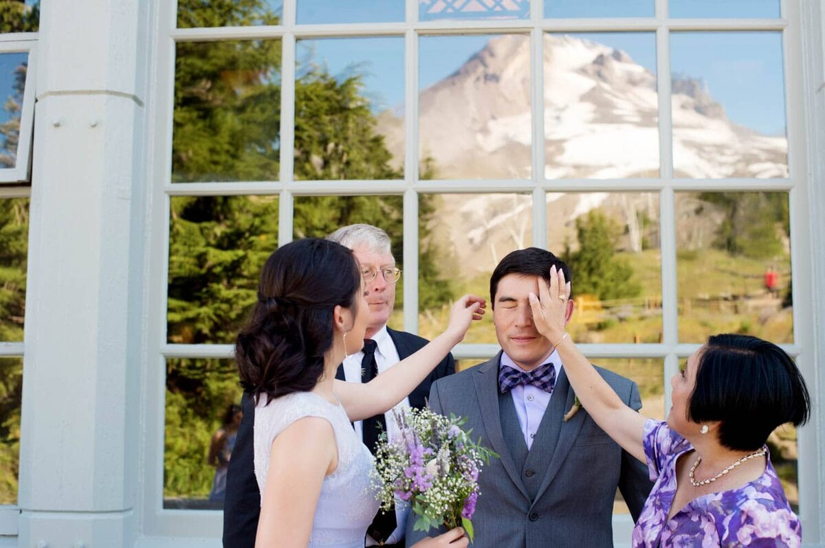 a mom and sister fix a groom's hair before his wedding with mt hood in background