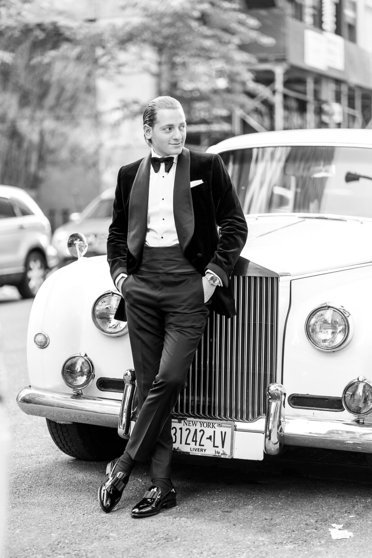 groom standing  with limo