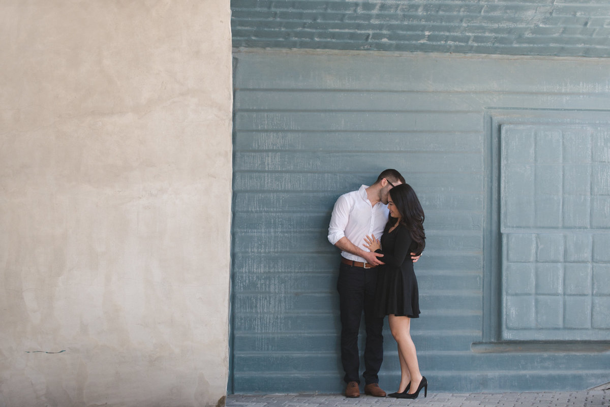 Couple cuddling against blue wall