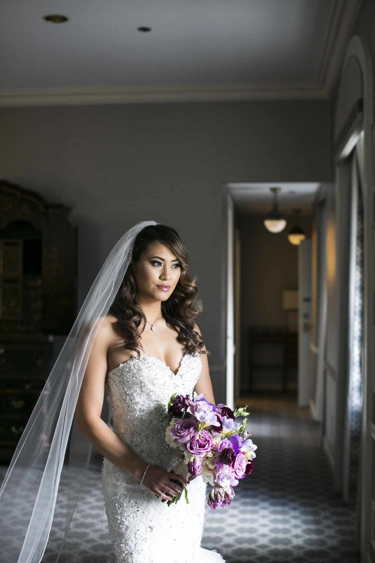 Our beautiful bride Mara holding a purple bridal bouquet.