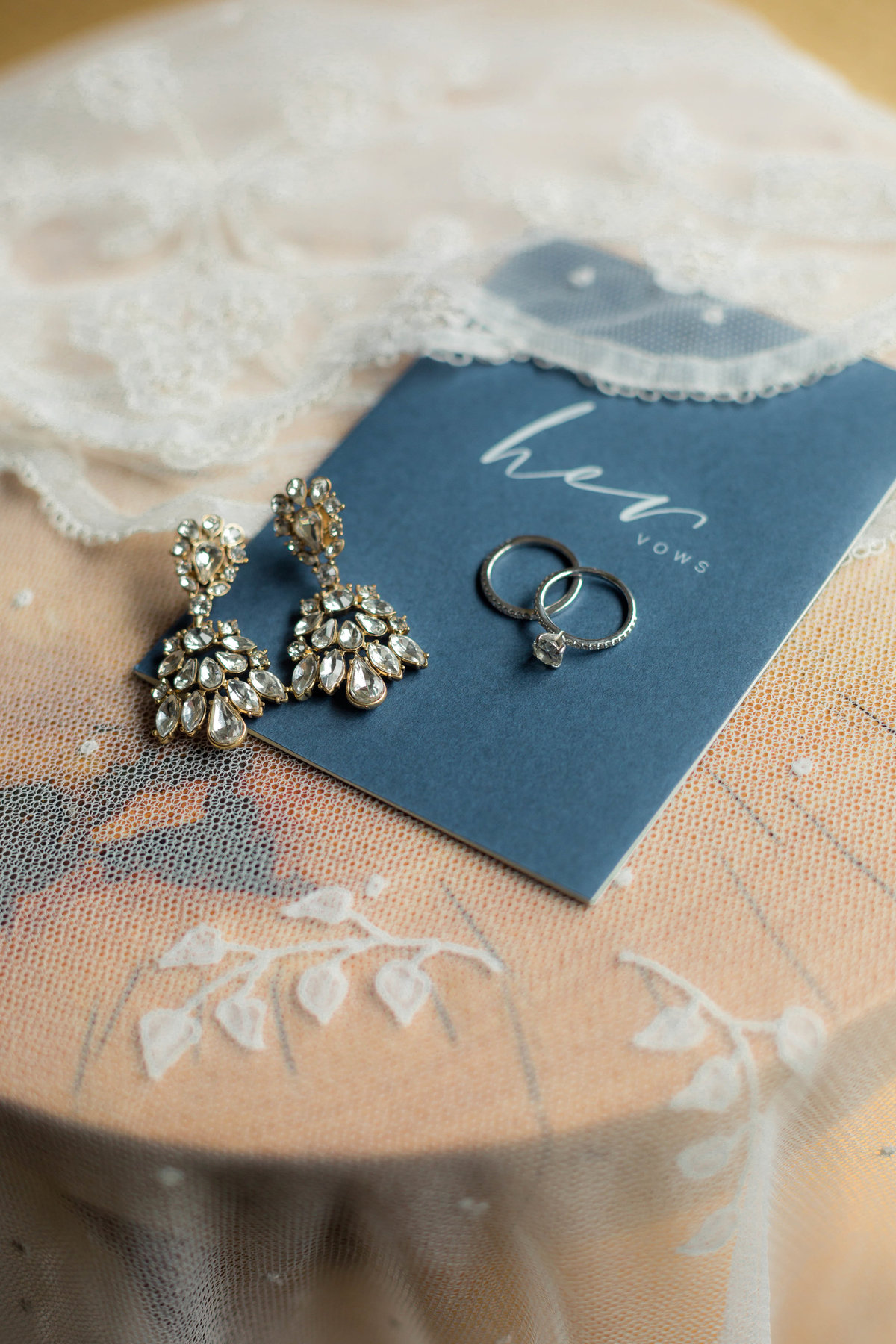 photograph of wedding rings and earrings on vintage veil