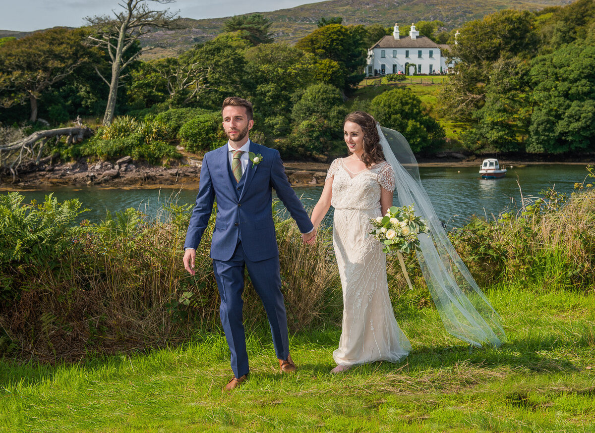 brunette bride wearing vintage, beaded wedding dress, holding a white bouquet and long veil walking with her groom who is wearing a navy suit with Westcove Georgian House in the background