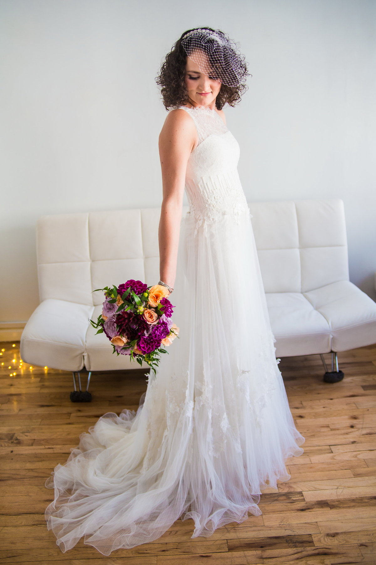 Bride in dress with brightly colored bouquet, at the Lofts at Prince, NYC