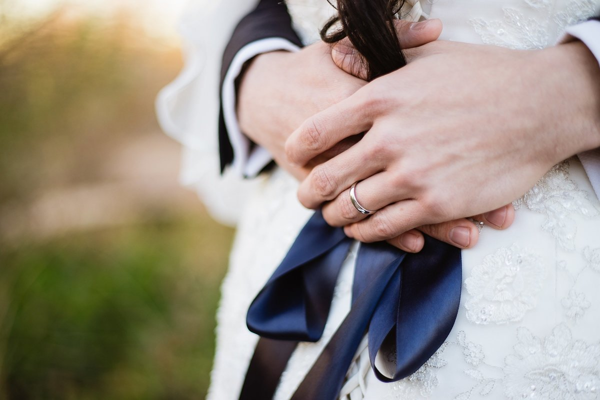 Groom's wedding ring as he holds his bride by Phoenix wedding photographer PMA Photography.