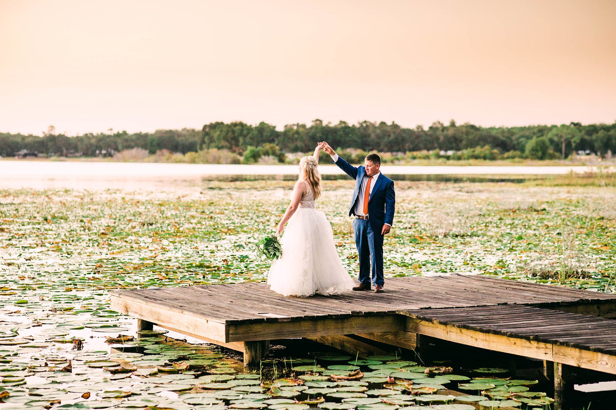 Wedding photos on dock surrounded by lilly pads in salt springs florida
