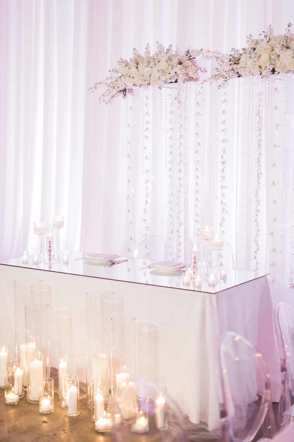 Head table framed by the wedding ceremony arch or white orchids