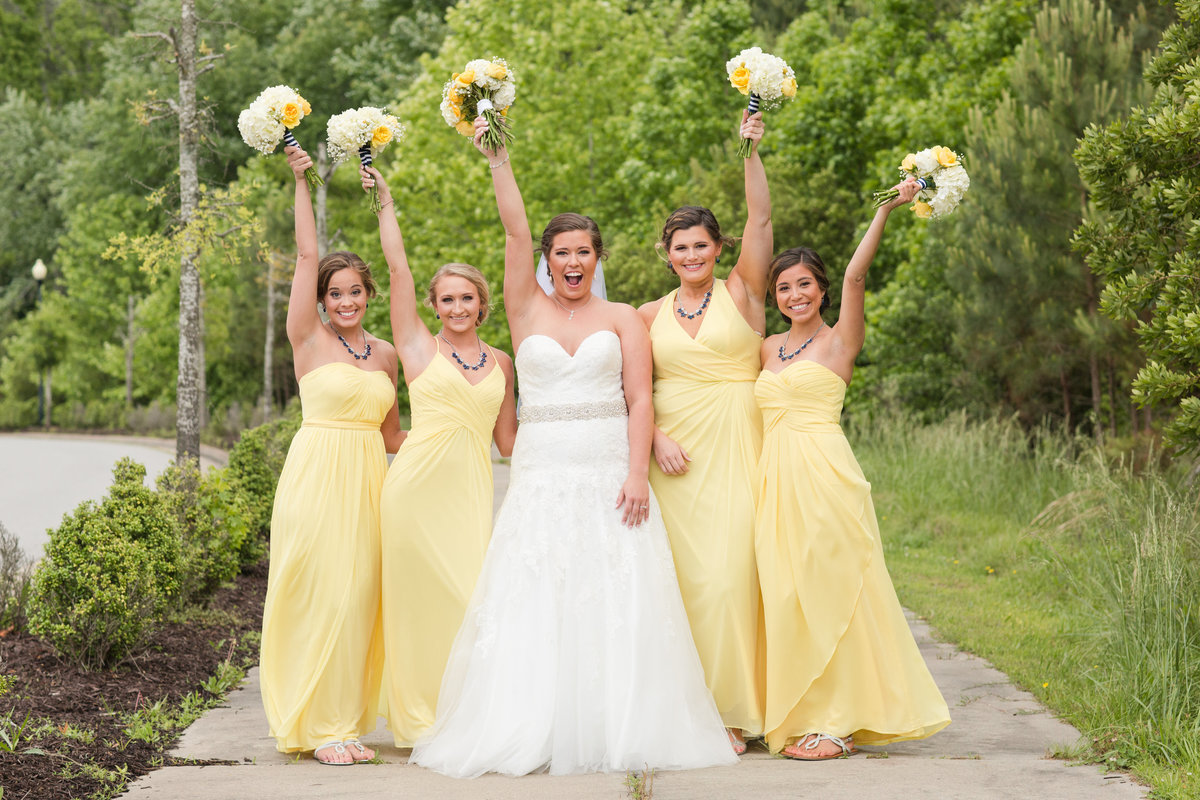 bridesmaids in yellow dresses cheering on a sunny day