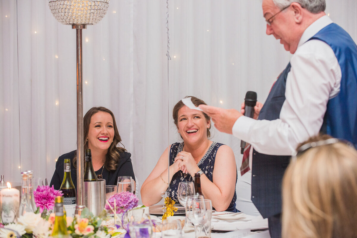 Dad giving wedding speech while the two brides laugh