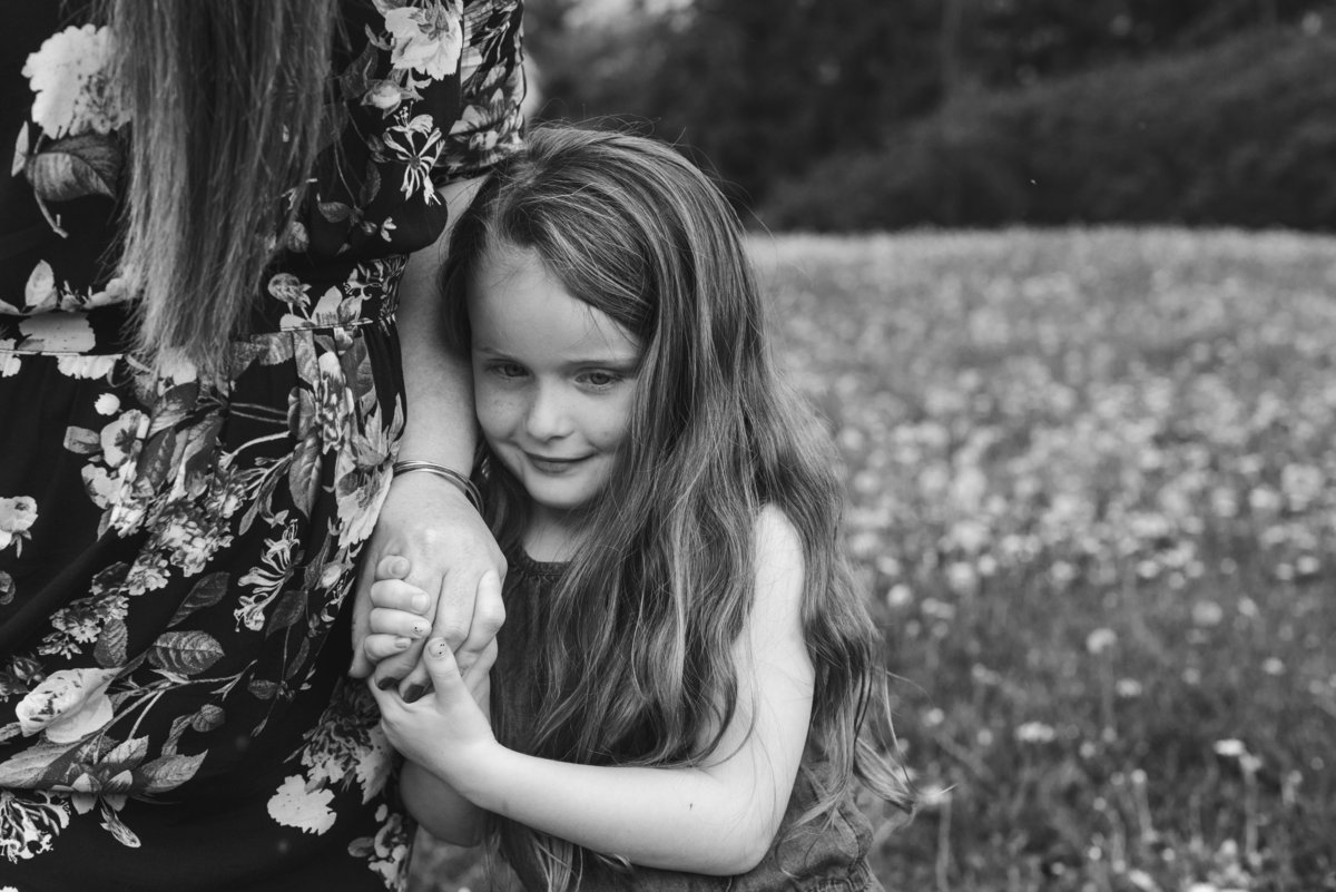 little girl holding her mom's hand in field of dandelions
