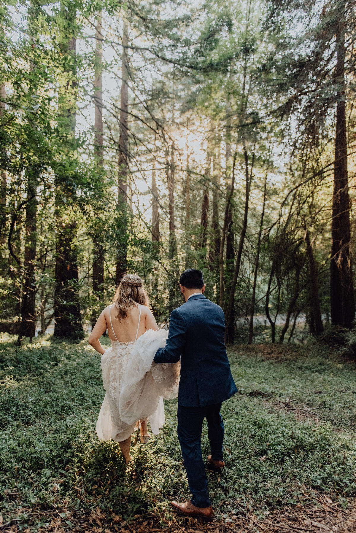 Bride and Groom walk through the forest as the groom holds the brides dress up for her