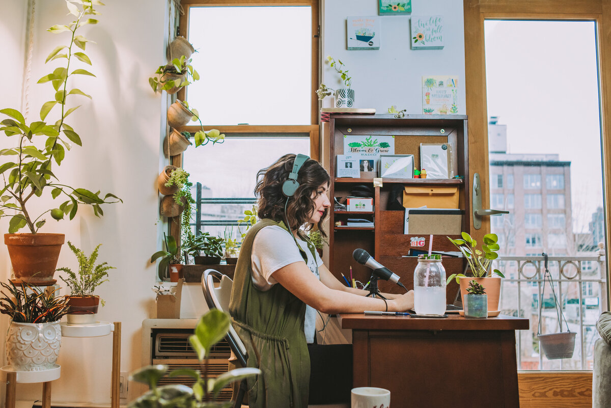 Podcast host, Maria, sits at her desk recording her podcast surrounded by potted plants