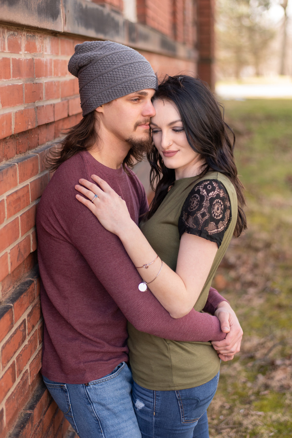 Young couple snuggling in embrace while leaned on brick wall