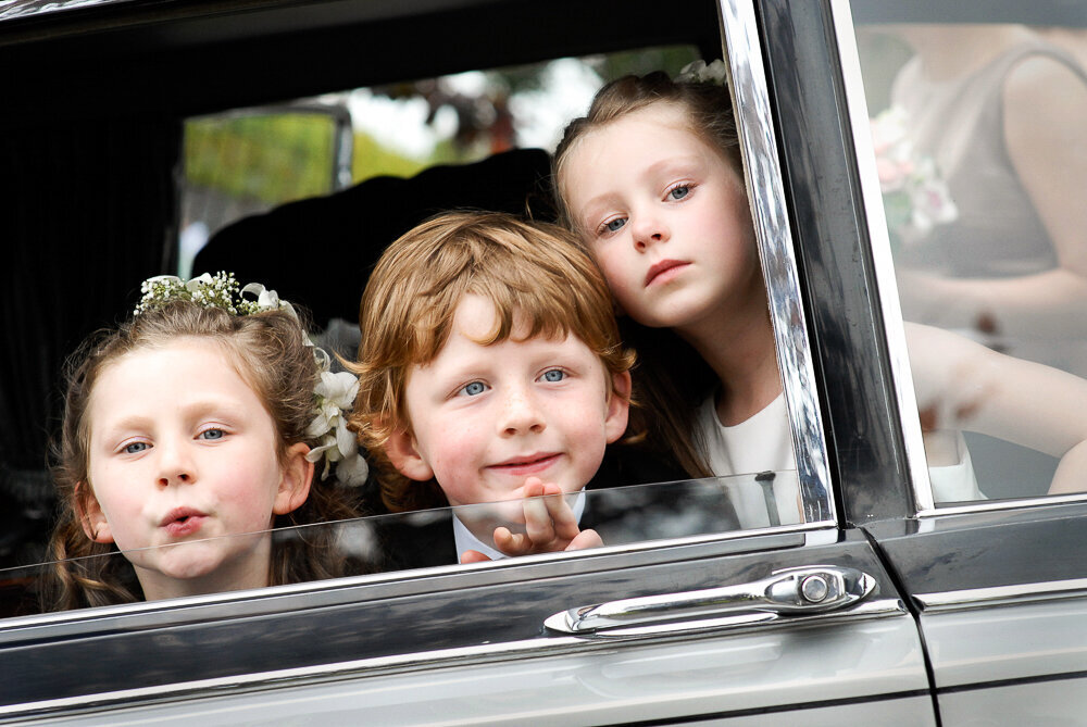 two flower girls and one page boy looking out the window of a vintage wedding car