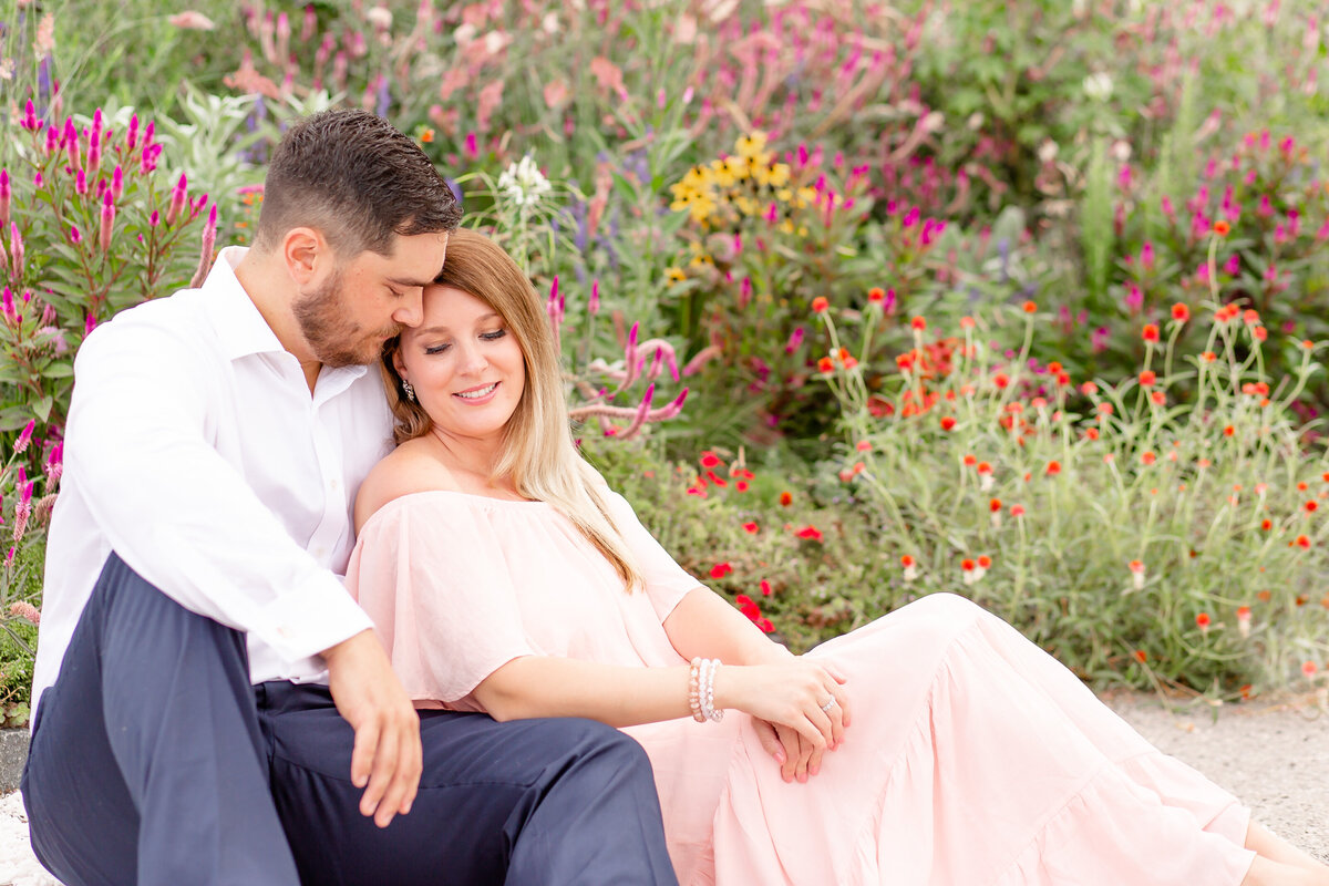 Summer Sunset Engagement Session with pink off the shoulder dress couple sitting by wildflowers at St. Louis Art Museum in Forest Park in St. Louis by Amy Britton Photography Photographer in St. Louis