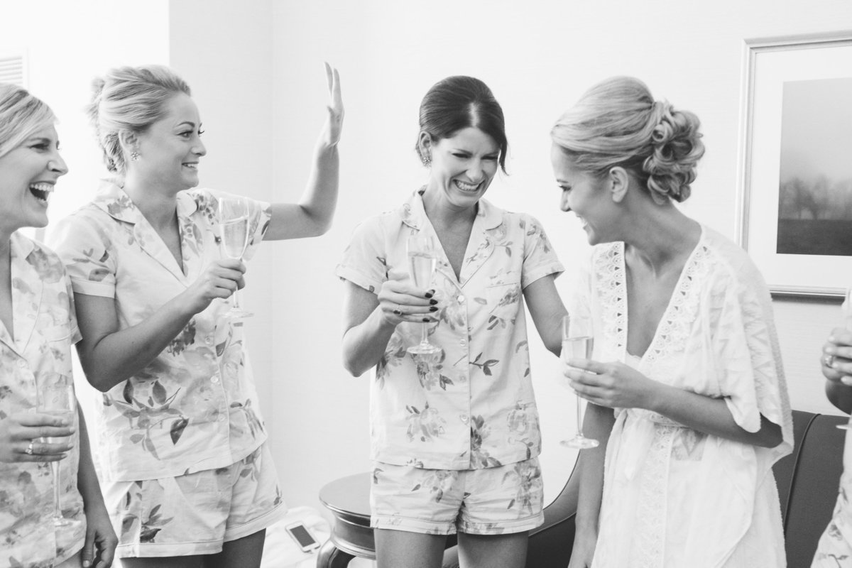 Bridesmaids try not to cry as they toast to the bride.  Real moment documented by photojournalist, Rebecca Cerasani.