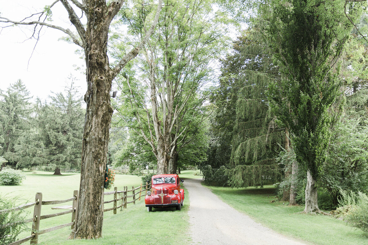 Tree lined driveway with red vintage pick up truck parked alongside