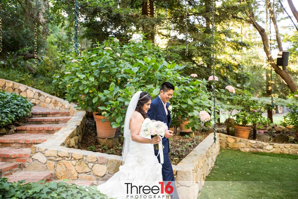 Bride and Groom exit the ceremony area through rock walls and stone steps at Calamigos Ranch