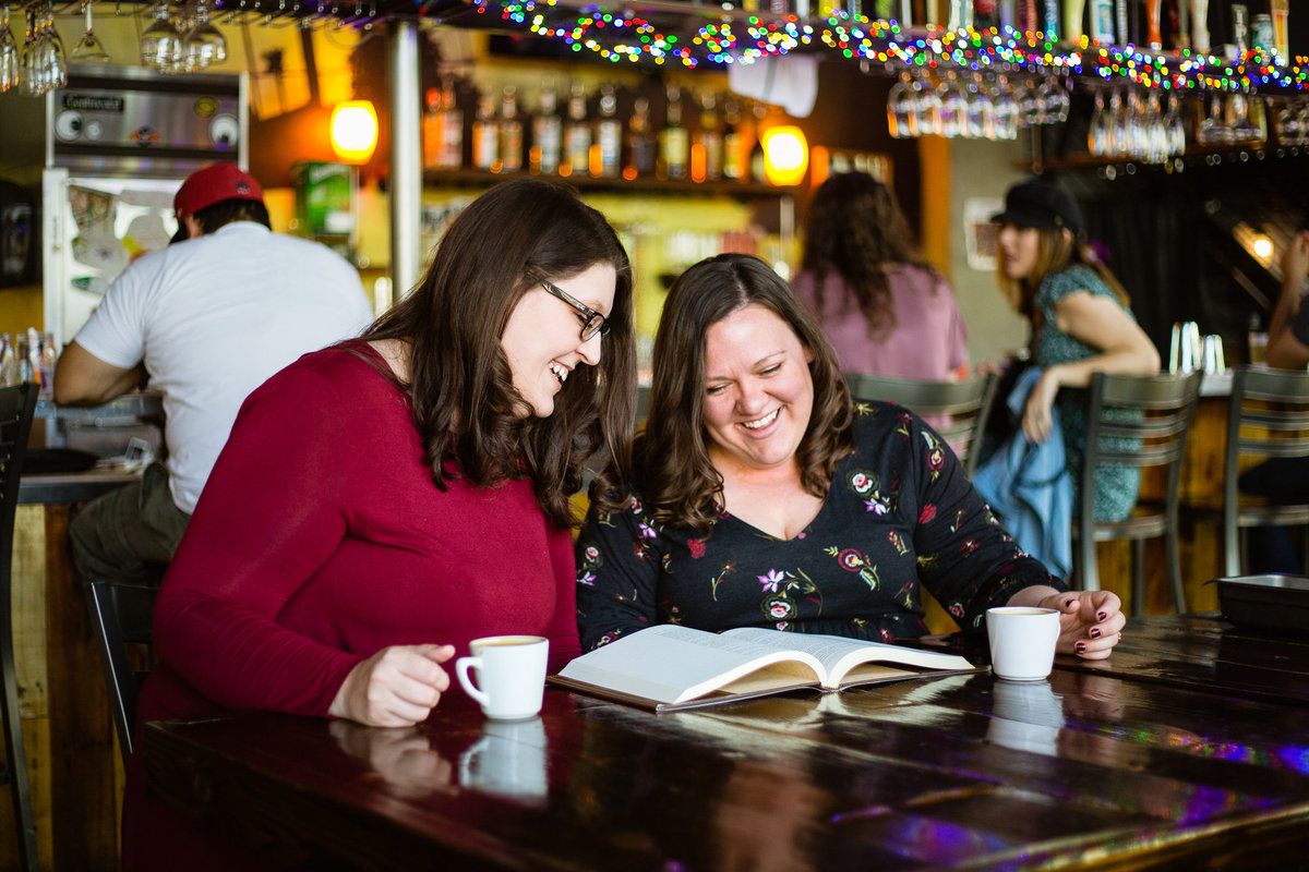 LGBTQ couple giggling together while reading a book at their coffee shop engagement session by Phoenix engagement photographer PMA Photography.