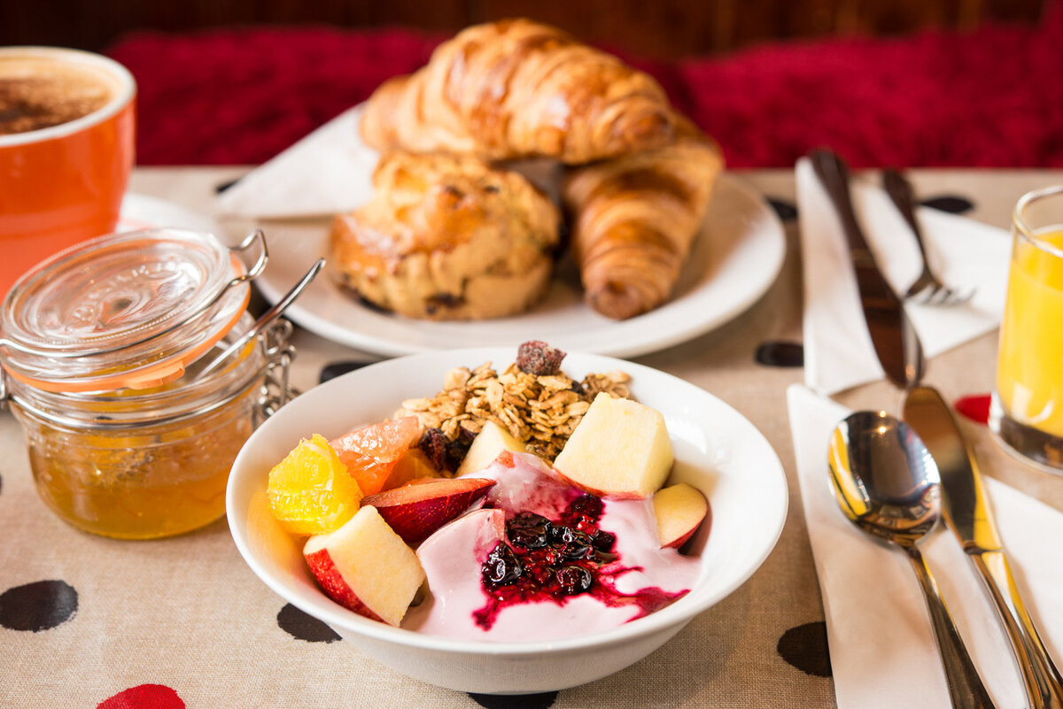 fruit, yoghurt, scone and croissants on a polka dot oilcloth