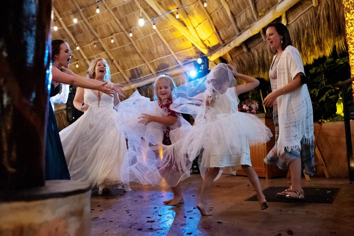 two little girls rip the tulle from the bride's wedding dress and run around dancing with it