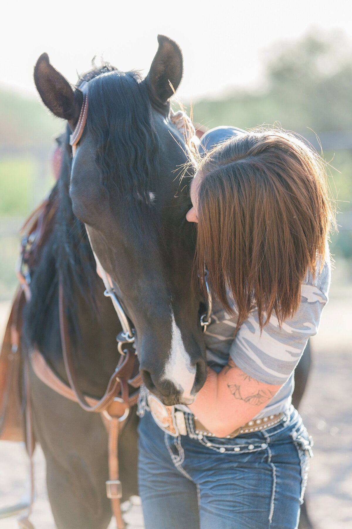 portrait of a girl hugging her horse as they are looking at each other
