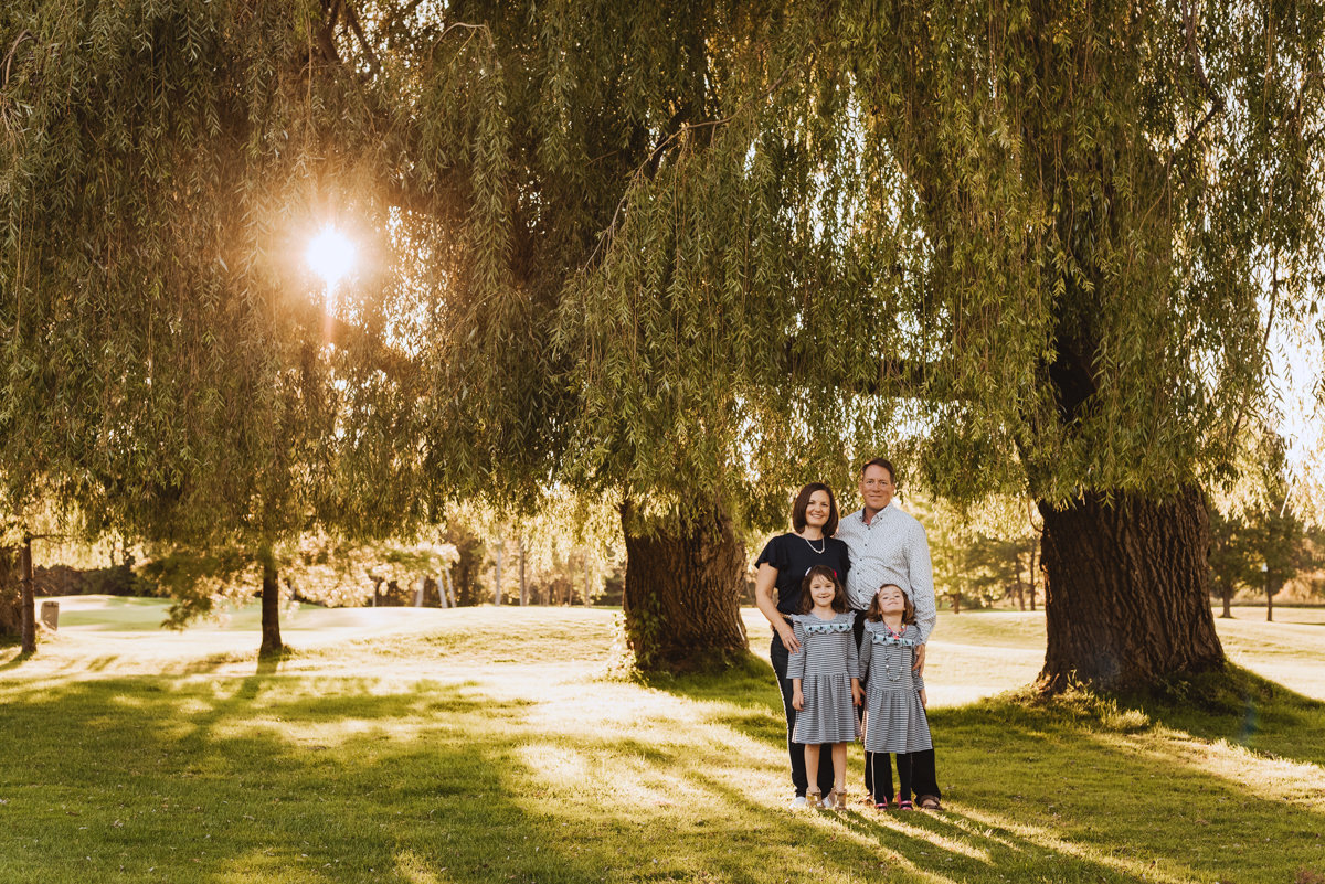 family underneath a willow tree at sunset