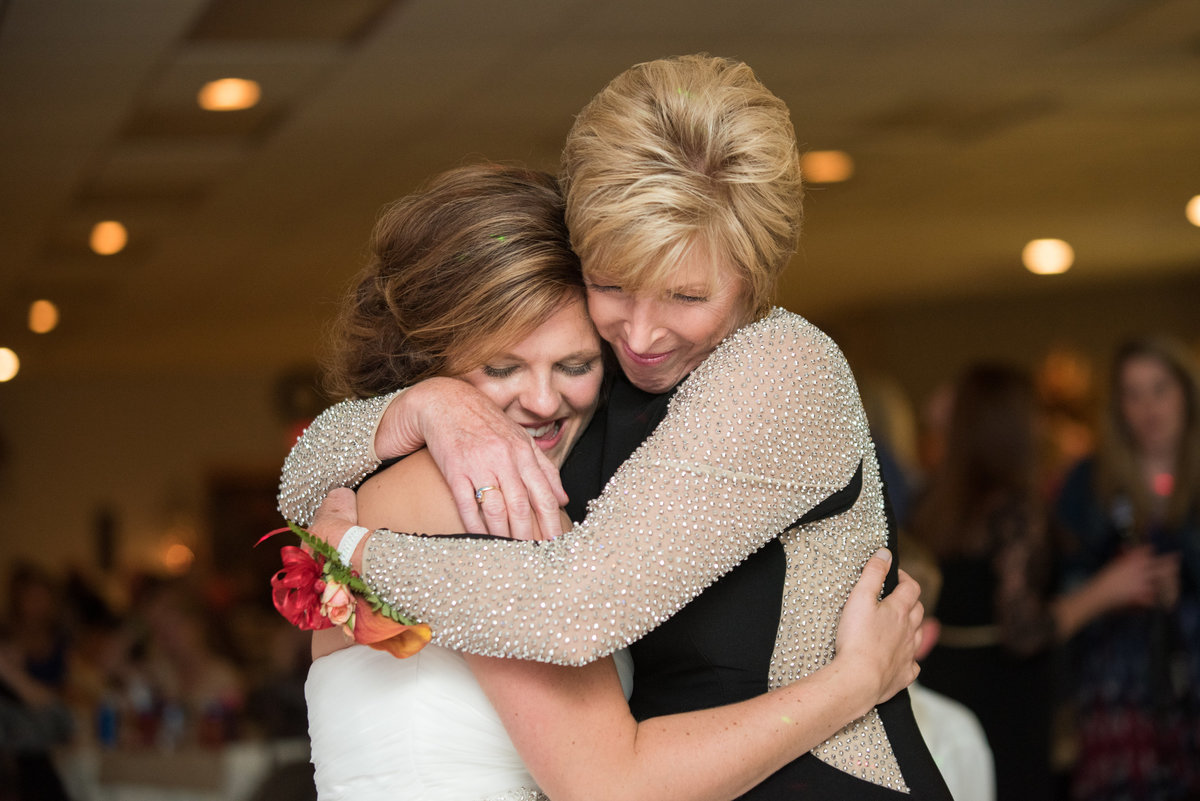 bride and mother are hugging at wedding