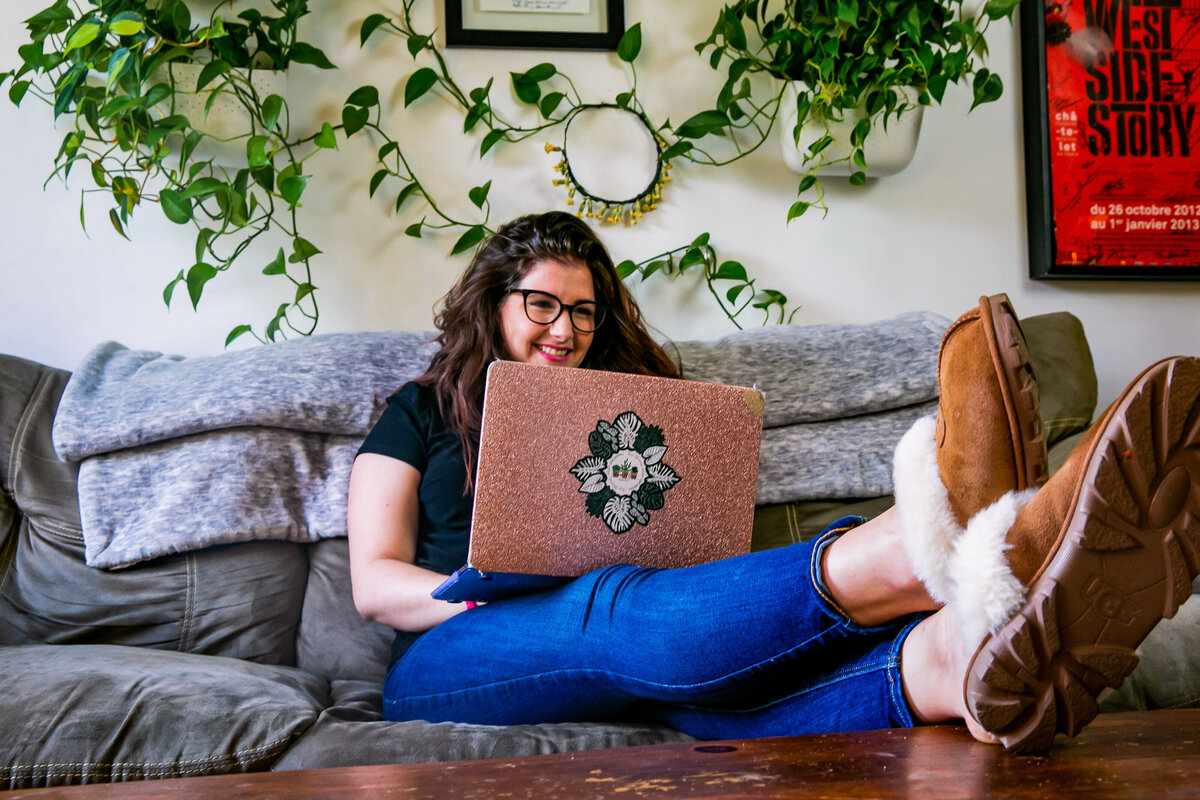 Host of Bloom & Grow Radio podcast, Maria,  sits on her sofa on her laptop surrounded by plants covering her wall