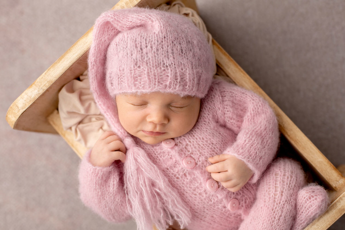 newborn girl dressed in pink smiles as she sleeps