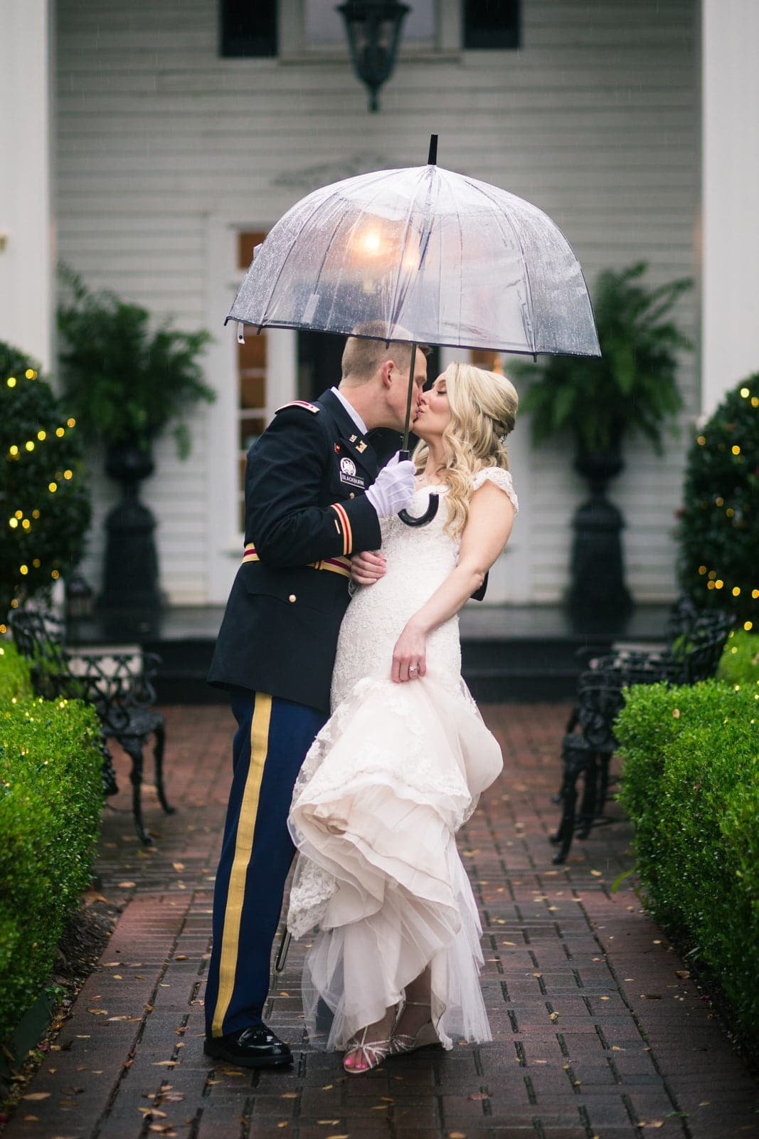 bride and groom kiss in the rain at Roswell Founders Hall